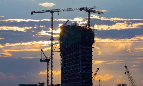 Unfinished concrete building with tower crane 1200px