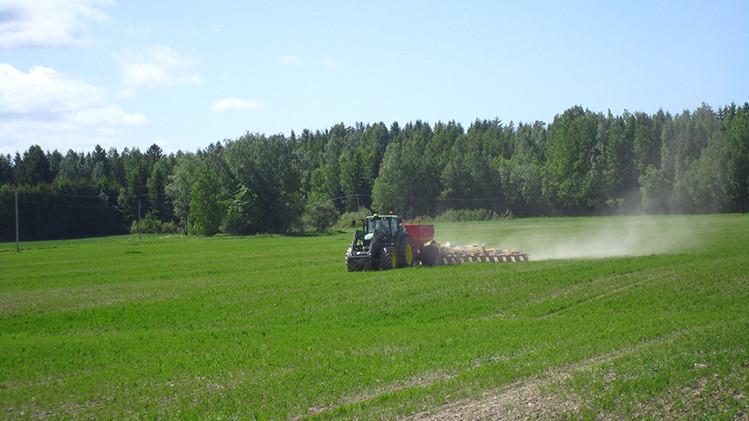 Traktor med ogräshacka på grönt fält.