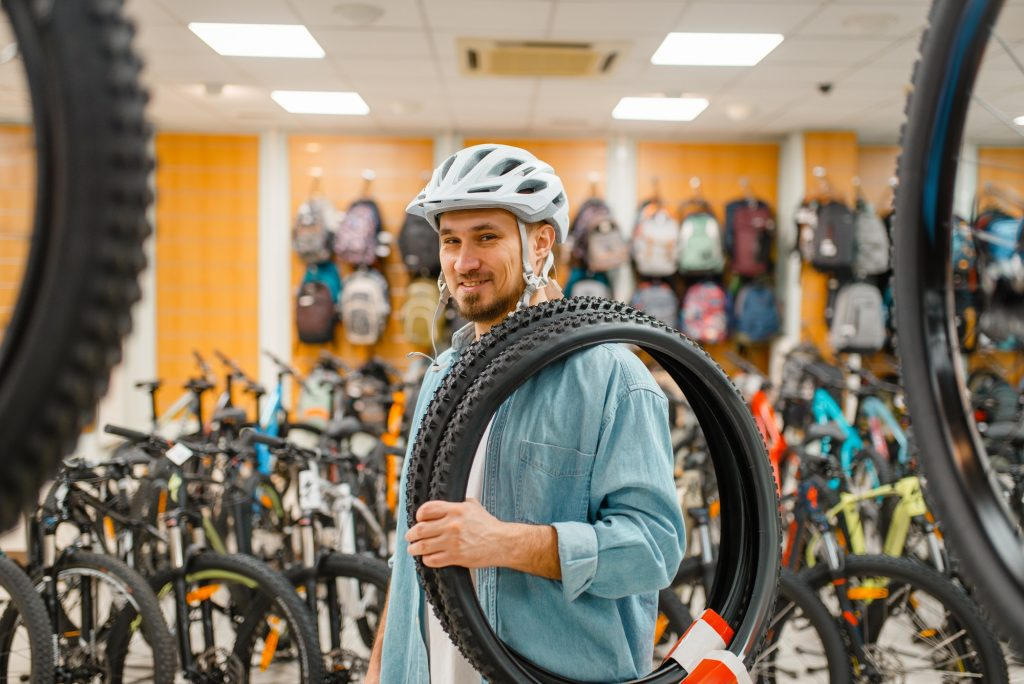 Man in cycling helmet holds bicycle tyre, shopping