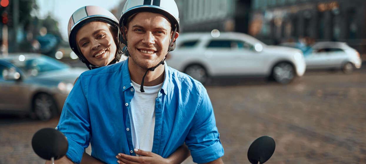 Man och kvinna på vespa på en trafikerad gata