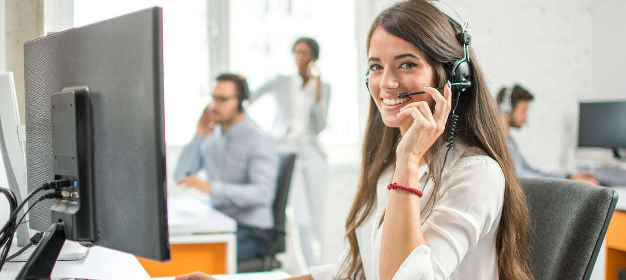 Kvinde med hovedtelefoner arbejder med flersproget kundeservice
