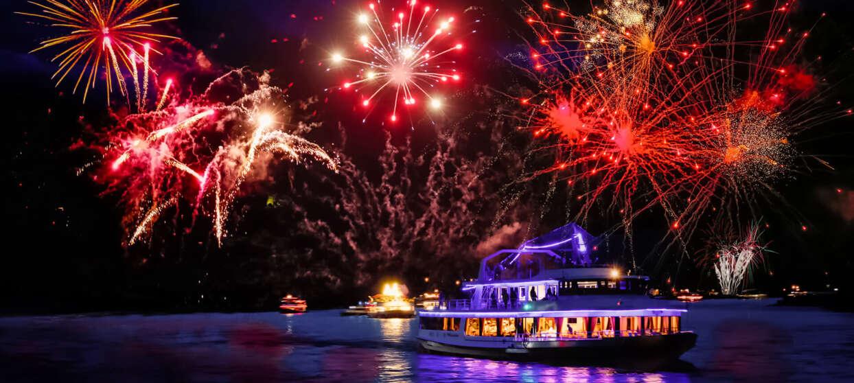 Båt i kvällsljus med fyrverkerier på himlen