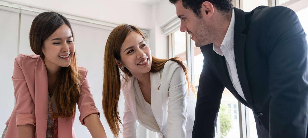 To smilende kvinner og en mann på et kontor, som diskuterer oversettelsesbehovene sine