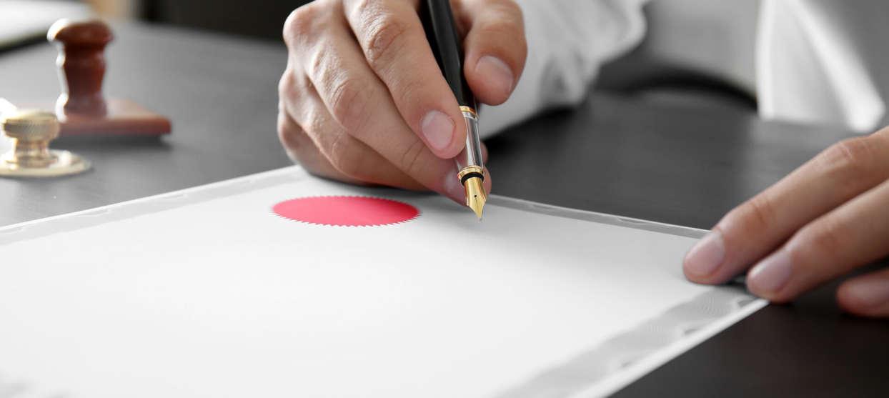 Person som håller reservoarpenna över papper