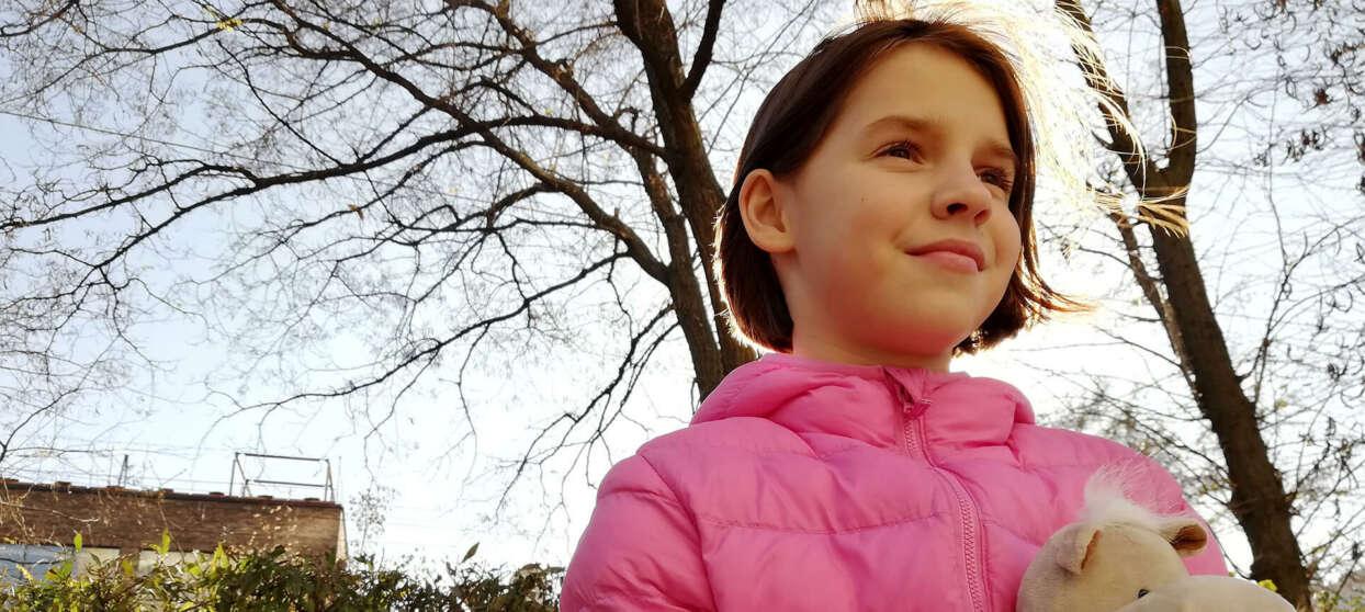 Ung tjej i rosa jacka och med gosedjur i famnen