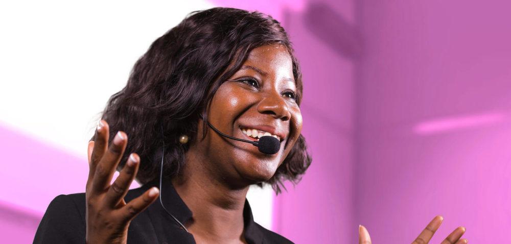 Kvinna med mikrofon som talar inför publik