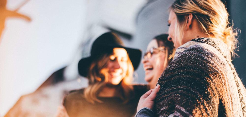 Tre glada kvinnor som står och pratar med varandra