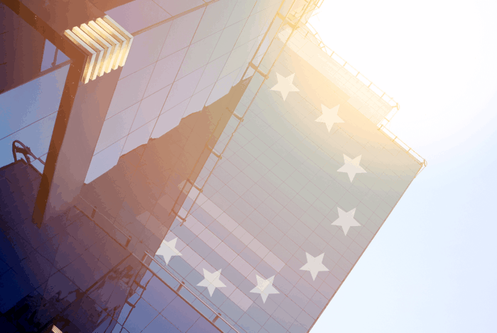 Skyskrapor i motljus med EU-stjärnor