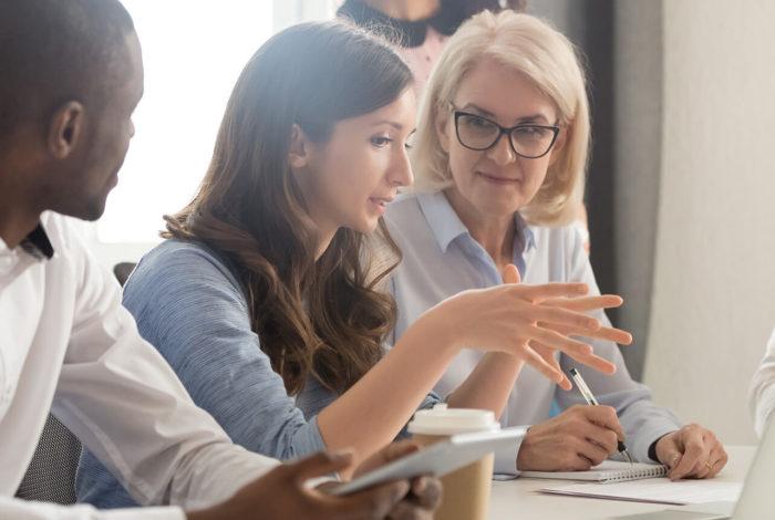Fyra personer diskuterar framför en dator.