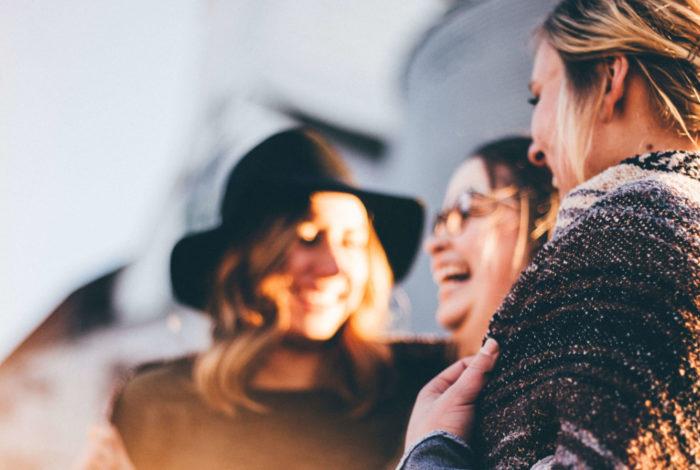 Tre glada kvinnor i samtal