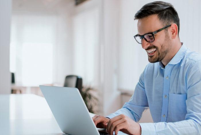 En leende man i blå skjorta vid dator