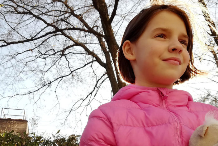 Young girl in pink jacket in a park